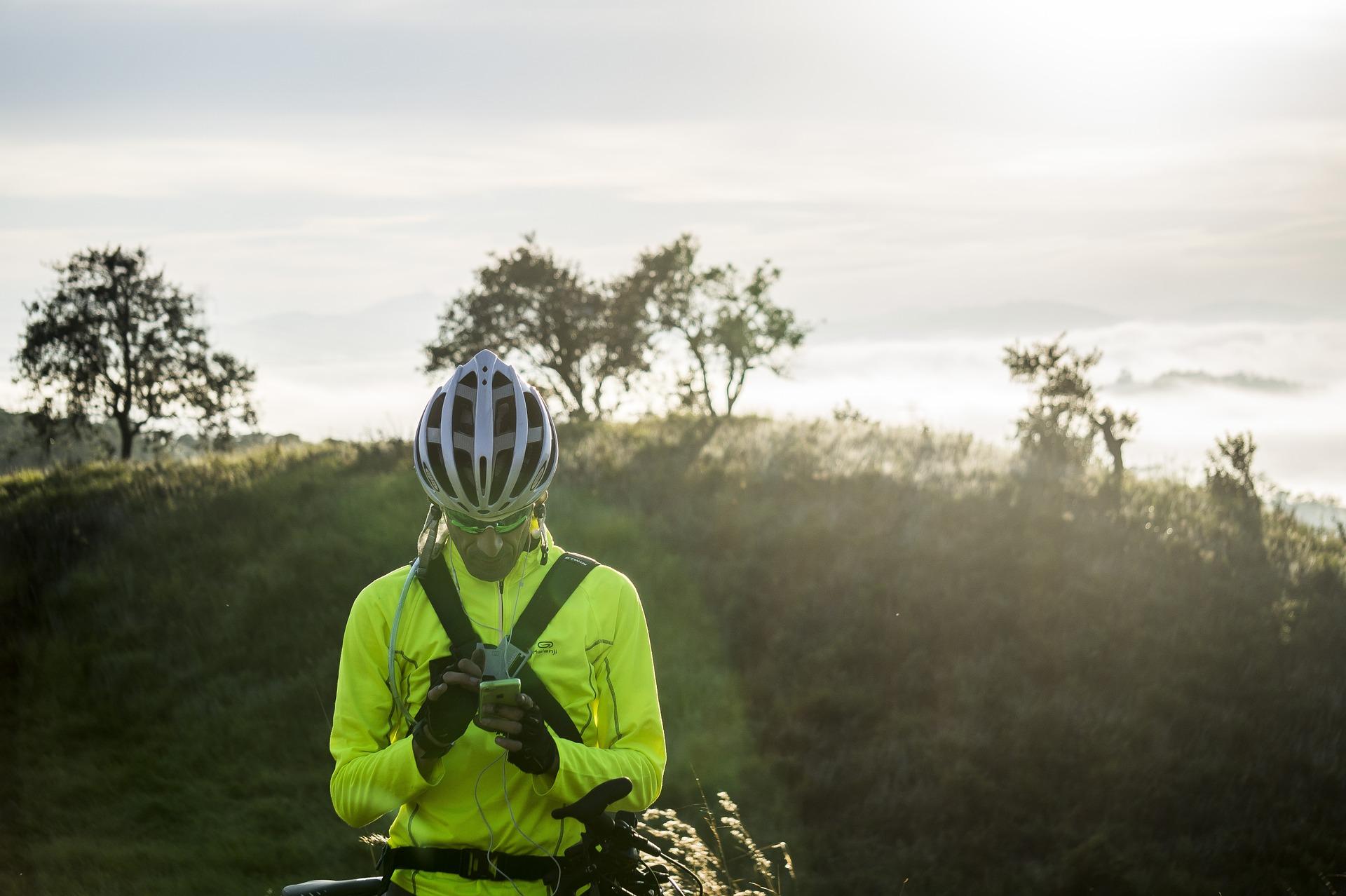 Imagem de um ciclista olhando o celular